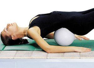 Девушка лежит на полу с мячом