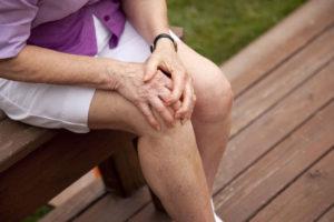 Женщина сидит и держится за колено