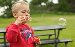Мальчик надувает мыльные пузыри