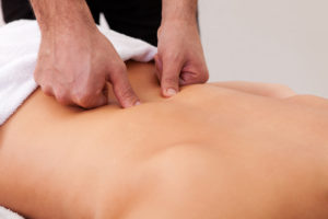 Руки массажиста и спина пациента