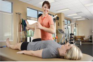 Врач помогает пациентке делать упражнение