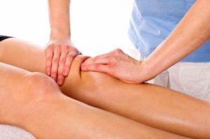 Человеку массируют коленный сустав