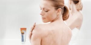 Девушка наносит крем на плечо