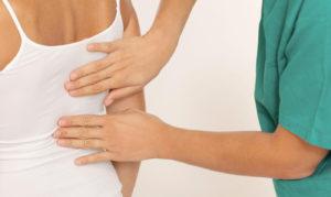 Руки врача на спине девушки