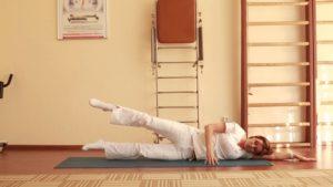 Женщина выполняет упражнение лежа