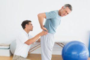 Врач обследует пациента с больной спиной