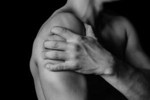 Мужчина держит свое плечо