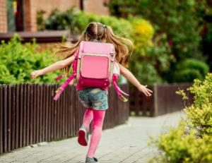 Девочка бежит по улице с рюкзаком