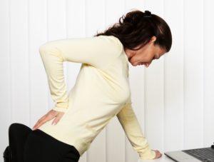 Женщина нагнулась и держится за спину