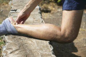 Мужчина согнул ногу и держится за ахиллово сухожилие