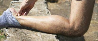 Мужчина согнул ноги и держится за ахиллово сухожилие