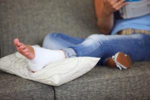 Женщина на диване с гипсом на ноге