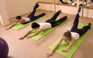 Пациенты выполняют упражнения на ковриках