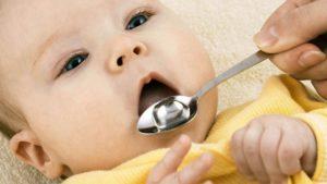 Маленькому ребенку дают ложку с лекарством